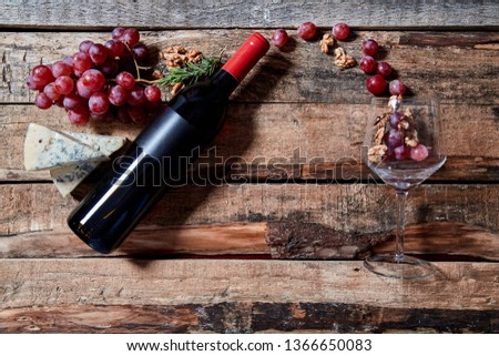 From above layout of grapes and walnuts flying from wine bottle into transparent wineglass on wood background #1366650083