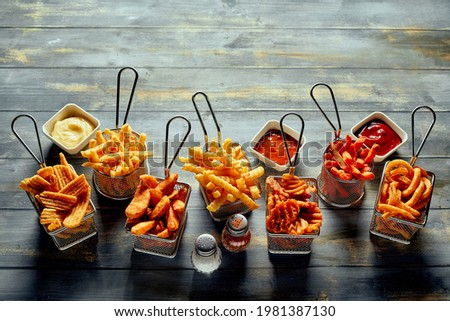 From above of appetizing fried potatoes chips waffle and crinkle fries served with mayonnaise ketchup and salt with pepper Stock photo ©