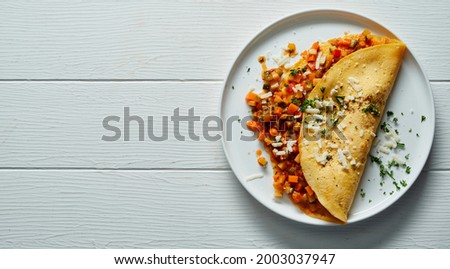 From above of appetizing omelette stuffed with vegetables served on plate on white wooden table Stock photo ©