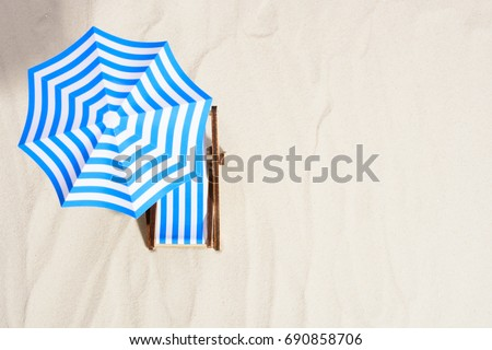 From above of lounge area on beach with striped chair under umbrella. #690858706