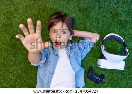 From above of stunned kid outstretching hand at camera while lying on meadow with VR glasses and gamepad