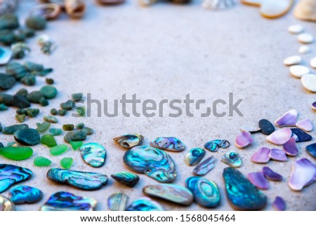 From above photo of shells, glass, stones, mother of pearl and Paua Shell in a circle - semi circle.  #1568045464