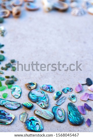From above photo of shells, glass, stones, mother of pearl and Paua Shell in a circle - semi circle.  #1568045467