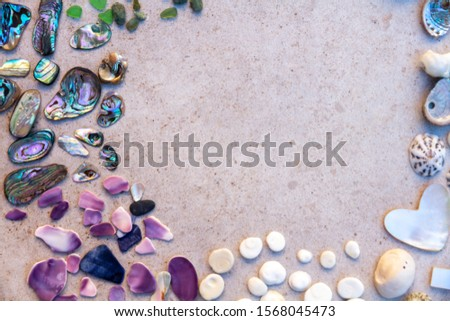 From above photo of shells, glass, stones, mother of pearl and Paua Shell in a circle - semi circle.  #1568045473