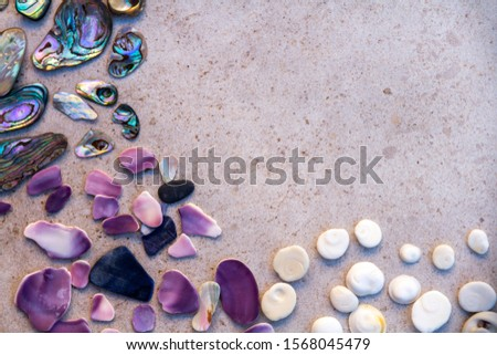 From above photo of shells, glass, stones, mother of pearl and Paua Shell in a circle - semi circle.  #1568045479