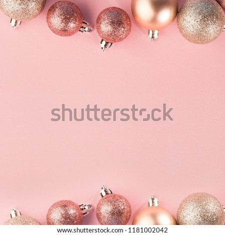 From above shot of bright glittering baubles composed in row on pink background. Christmas background. Christmas concept. Square picture