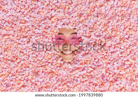 From above shot of happy cheerful woman poses around pile of pink soft sweet marshmallows enjoys eating appetizing snack wears heart shaped sunglasses. Face of smiling female model through dessert Stock photo ©
