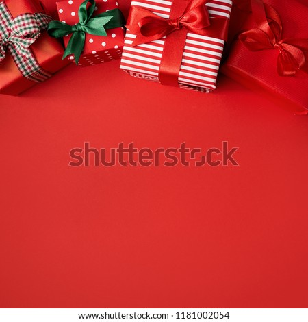 From above view of few wrapped beautiful gifts decorated with colorful ribbons and composed on red. Square format. Christmas concept #1181002054
