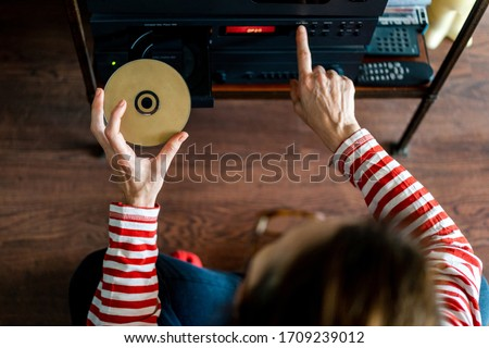 from above woman dressed in red striped t-shirt putting a compact disc or cd into a stereo in the interior of a house Сток-фото ©
