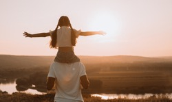 From behind joyful man and girl spending time together while having shoulder ride on sunset