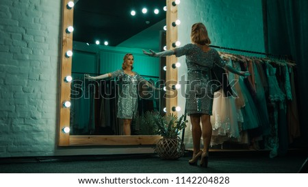 From below back view of beautiful singer in short sparkling dress and gloves standing in front of mirror practicing show