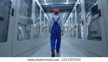 From below back view of Korean man in overall and hardhat walking in corridor with electrical equipment of solar power station