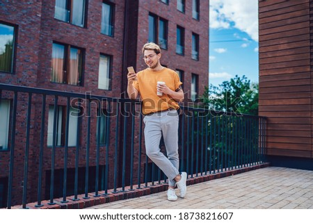 From below cheerful optimistic stylish male watching smartphone joyfully during leaning on street fence with coffee to go in summer day Stockfoto ©