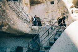 From below male tourist with backpack and map walking down sand stairs and holding rails in ruins of historical ancient city