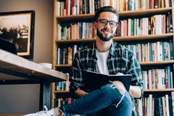 From below of bearded young guy with trendy hairstyle and stylish outfit sitting in cozy library reading book in daylight