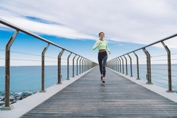 From below of concentrated sportive female in activewear running on pier next to sea in sunny summer day in city