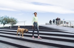 From below of full body cheerful female in activewear walking dog on leash down street steps of city located near sea