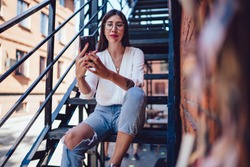 From below of smiling smart  slim young lady in glasses in white shirt ripped jeans sitting on iron stairs of brick building making selfie  on mobile phone in street