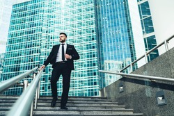 From below of successful businessman in suit walking down stairs in hurry looking away in front of giant modern business center