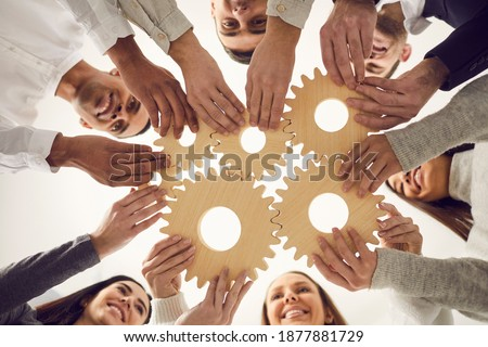 From below of team of young creative multicultural people joining gear wheels together as metaphor for effective teamwork, unity, collaboration, finding working solution and creating business system