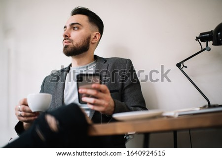 From below pensive adult male in formal clothes with hot drink in white cup and smartphone looking away at desk in office