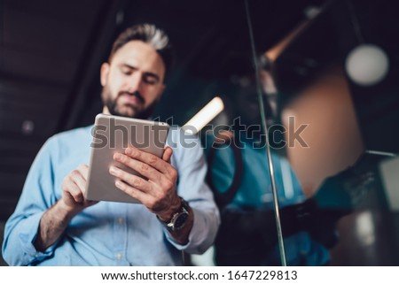 From below soft focus of bearded man in open office near glass wall holding tablet and focusing on work tapping screen