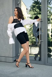 From below view of young female model wearing bike shorts, sandals on heels, tie and white shirt running downstairs. Fashionable brunette caucasian woman hurrying near office building, looking aside.