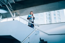 From below young pleased lady in casual clothes with papers making phone call while walking down exterior stairs of modern high rise building in daytime