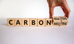 From carbon neutral to negative. Hand flips cubes and changes words 'carbon neutral' to 'carbon negative'. Beautiful white background, copy space. Business, ecological and carbon negative concept.