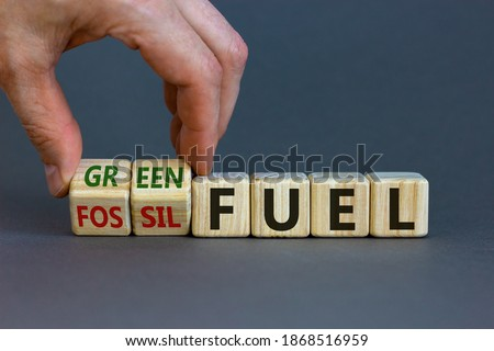 Photo of  From fossil to green fuel. Male hand turns cubes and changes the words 'fossil fuel' to 'green fuel'. Beautiful grey background. Business and green fuel concept. Copy space.