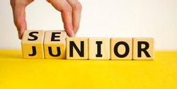 From junior to senior symbol. Businessman turns cubes and changes the word 'junior' to 'senior'. Beautiful yellow table, white background, copy space. Business and junior or senior concept.