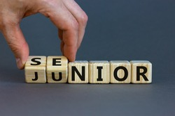 From junior to senior symbol. Businessman turns cubes and changes the word 'junior' to 'senior'. Beautiful grey background, copy space. Business and junior or senior concept.