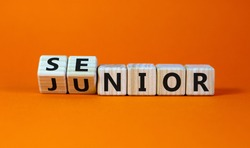 From junior to senior symbol. Turned cubes and changed the word 'junior' to 'senior'. Beautiful orange background, copy space. Business and junior or senior concept.