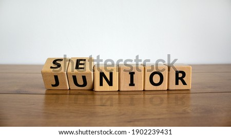 From junior to senior symbol. Turned cubes and changed the word 'junior' to 'senior'. Beautiful wooden table, white background, copy space. Business and junior or senior concept. Stock photo ©
