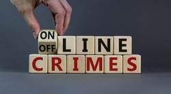 From offline to online crimes. Male hand flips a cube and changes the words 'offline crimes' to 'online crimes'. Beautiful grey background. Copy space. Business and online crimes concept.