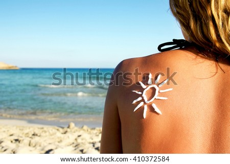 from sun cream on the female back on the seaside #410372584