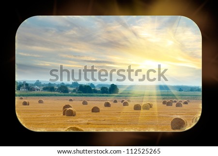 From the windows of the train can be seen field with bales of straw illuminated by the rays of the sun