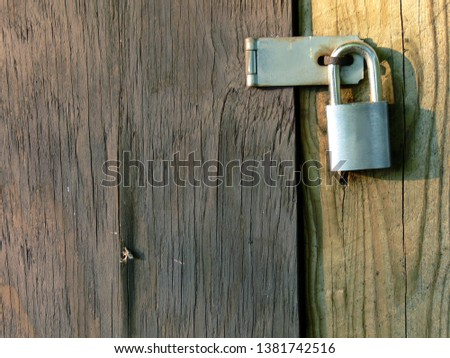 Front closeup shot of an old wooden plank door of a barn locked with a pad-lock showing wooden texture, grains and rust on the latch