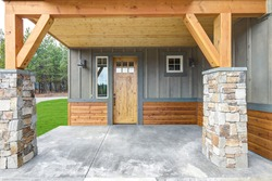 Front covered entrance to a new rustic natural townhome with concrete patio and stone columes.