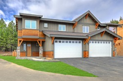 Front covered entrance to a new rustic natural townhome with concrete patio and stone columes and white garage doors.