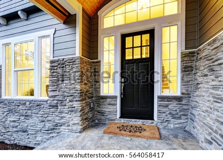 Front covered porch design boasts stone siding which creates immense curb appeal of luxurious home. Welcome mat lead to black front door accented with sidelights framed by white siding. Northwest, USA