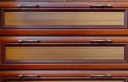 Front decorative panel of chest of drawers. Exquisite wooden surface of sliding cabinet shelves with handles