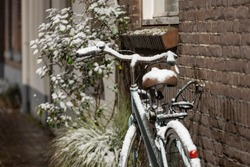 Front door exterior of a home with a vintage authentic bicycle locked to the facade wall in Zutphen after snowfall with snow on the stylish city bike