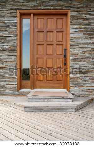 Front door made from glass and wood near a stone wall