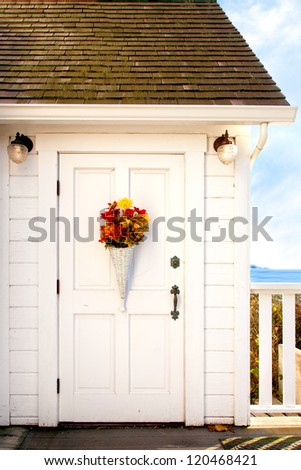 Front door of a seaside cottage painted white with vintage hardware and decorated with a basket of flowers.