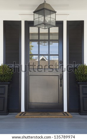 Front door of an upscale home/Vertical shot of a black front door on an upscale home with reflection in the windows and view of plants, doormat, and light fixture.