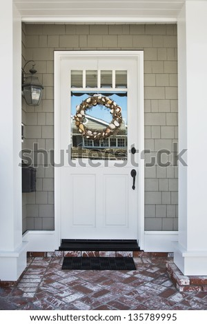 Front door of an upscale home/Vertical shot of a white front door on an upscale home with a wreath, brick, and reflection in the windows