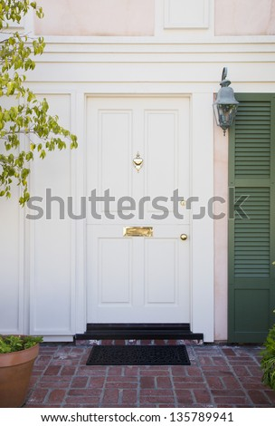 Front door of an upscale home/Vertical shot of a white front door with brass accents and green stutters on a home with view of brick, mail slot and door mat.