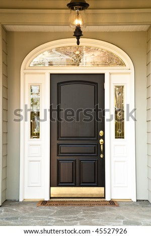 Front door of an upscale home with an illuminated porch light Vertical format