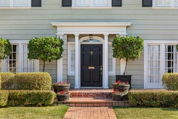 Front door of classic home with landscaped front yard and brick path.